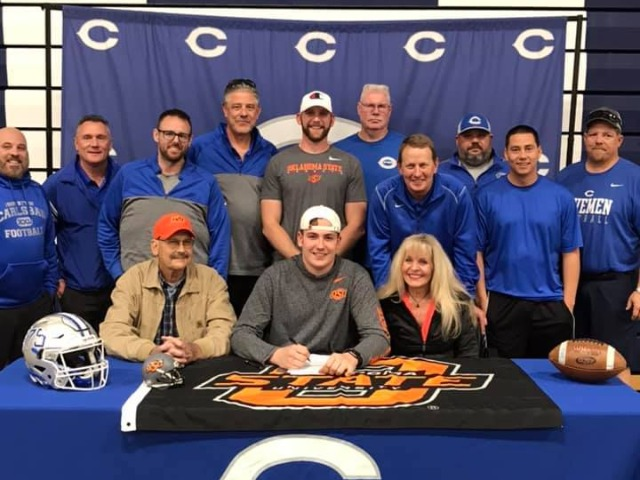 Taylor Miterko signs his scholarship to play football for Oklahoma State University