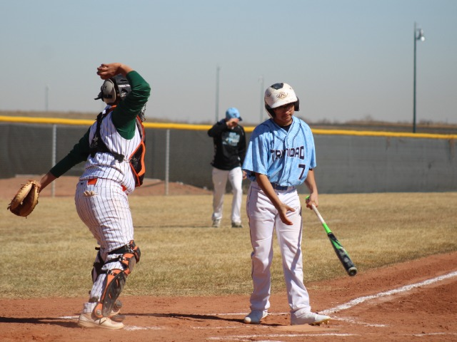 dams City catcher Victor Campos celebrates a strikeout as Trinidad's Justin Sintas starts to head back to the dugout.