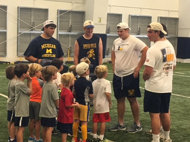 """Varisty Offensive Lineman coaching up some future Scots at the """"Tackle World Hunger"""" clinic on 8/25/18"""