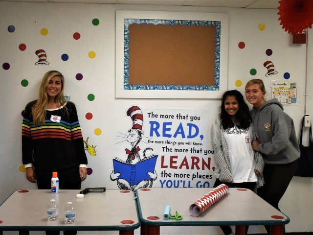2019 Community Service Project - Voice of Hope - Junior Georgia Holsomback, Sophomore Dharma Kikkeri, and Junior Chloe Kanaan showing off their classroom wall.