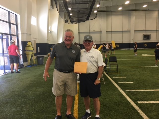 "Coach Allen donating the $1908 to the ""Tackle World Hunger"" Ministry"
